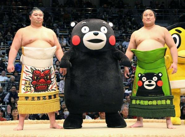 熊本県出身力士の正代(左)と佐田の海(右)と土俵に上がるくまモン。佐田の海の化粧まわしはくまモン